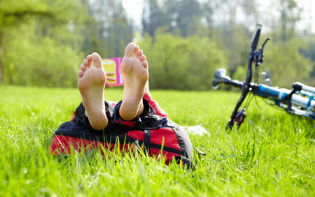 Barefoot cyclist on a halt reads lying in fresh green grass  Enjoying relaxation outdoors Stock Photo