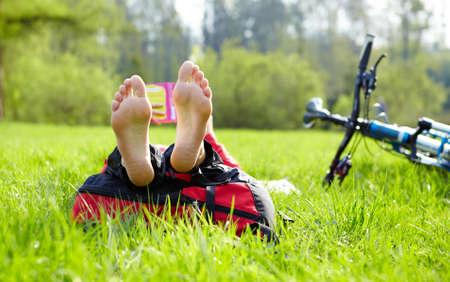 halt: Barefoot cyclist on a halt reads lying in fresh green grass  Enjoying relaxation outdoors Stock Photo