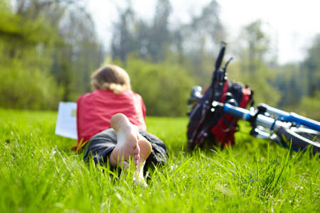 Girl cyclist on a halt reads on green grass outdoors in spring park  Enjoying relaxation