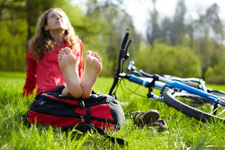 Happy girl cyclist enjoying relaxation sitting barefoot outdoors in spring sunny park Stock Photo