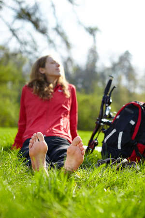 Happy girl biker enjoying relaxation sitting barefoot in green grass outdoors in summer sunny park photo