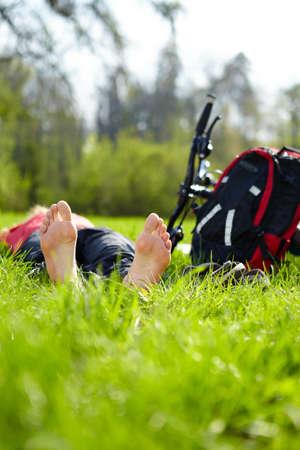 Barefoot biker enjoying relaxation lying in fresh green grass outdoors in summer sunny park