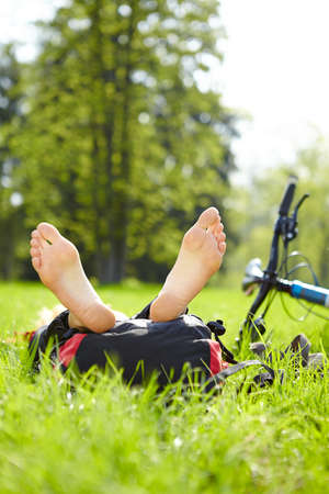 Happy cyclist enjoying relaxation lying barefoot in green grass outdoors in summer park photo