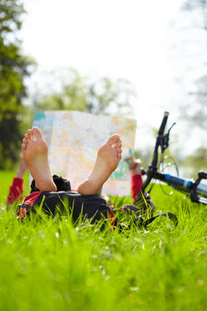 Girl cyclist on a halt reads a map lying on green grass outdoors in spring park  Enjoying relaxation photo