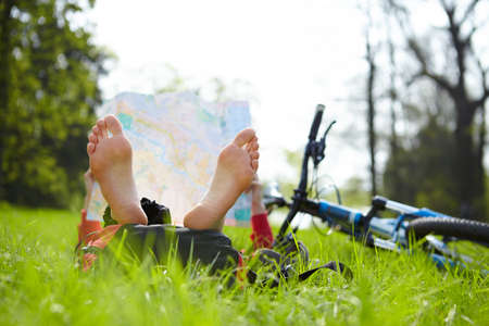 Girl cyclist reads a map lying barefoot on green grass outdoors in summer park  Enjoying relaxation