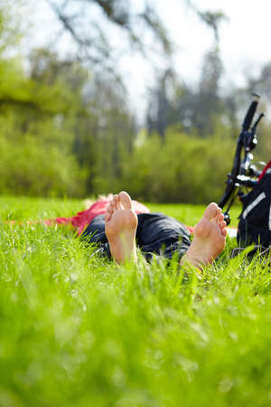 Barefoot tourist enjoying relaxation lying in fresh green grass outdoors in summer sunny park