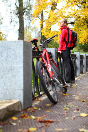 Young woman cyclist with bike and backpack on bridge enjoy vacation in autumn park  Bicycle walk in weekend photo