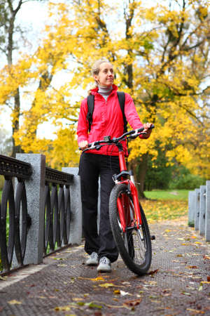 Young girl cyclist with bike on bridge in autumn park against the background of golden nature photo