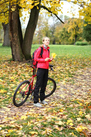 bicycle walk: Young girl cyclist with bike enjoy vacation in autumn park  Bicycle walk in weekend