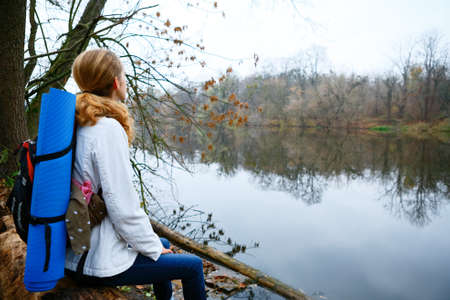 Woman hiker resting on the riverbank. Walking in the weekend photo