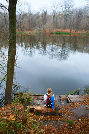 Woman hiker relax on the riverbank. Active Lifestyle photo