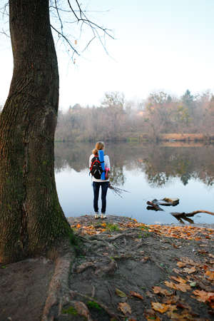 Woman hiker stand and relax on the riverbank. Active Lifestyle photo