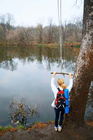 riverside trees: Woman hiker with bungee in the hands near autumn river. Active Lifestyle