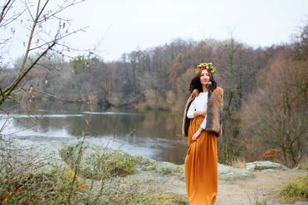 Autumn young woman with flower wreath in fur coat outdoors near the pond. Beauty concept photo