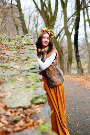 Autumn woman with flowers wreath near a stone wall. Autumn season photo
