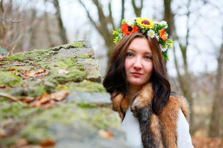Autumn woman portrait with flowers wreath in fur coat near a stone wall. Autumn season photo