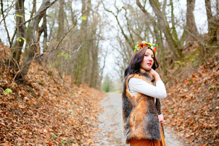 Beautiful woman with flower wreath in fur coat outdoors in the autumn park. Beauty concept photo