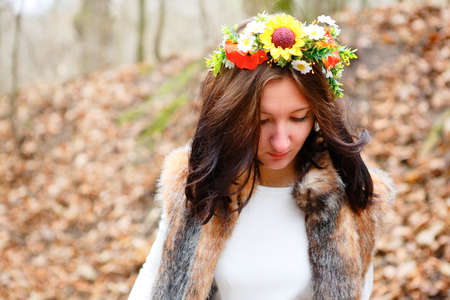 Beautiful woman with flowers wreath in autumn park. Beauty concept photo