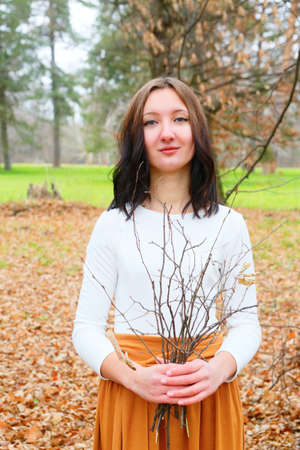 Autumn young woman with dry twigs in her hand. Natural concept photo