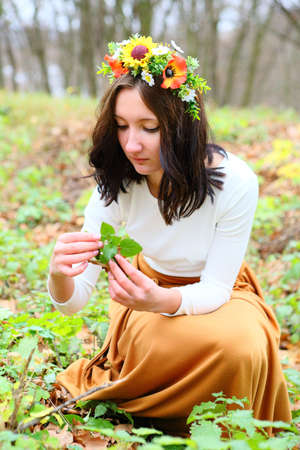 Beautiful girl with flower wreath on her head with leaves in her hands in the autumn nature photo