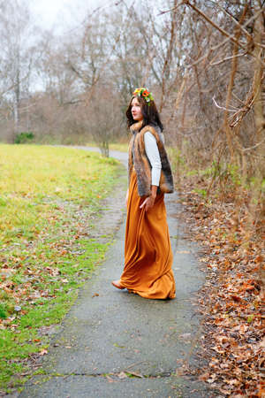 Young girl with flowers wreath in fur coat goes along the asphalt path in a autumn park photo