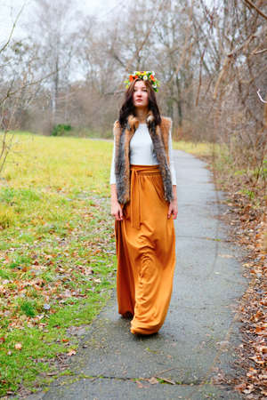 Young woman with flowers wreath in fur coat goes along the asphalt path in a autumn park photo