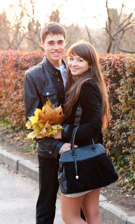 Happy beautiful couple with the maple leaf in hand in outumn outdoors photo