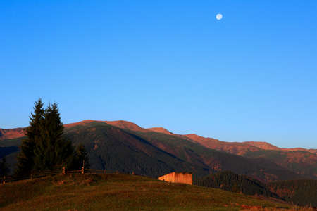 Mountain landscape with the moon and barn early morning. Carpathians mountains, Ukraine, Europe photo