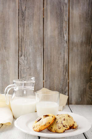 Tasty cookies and milk on wooden background, food photo