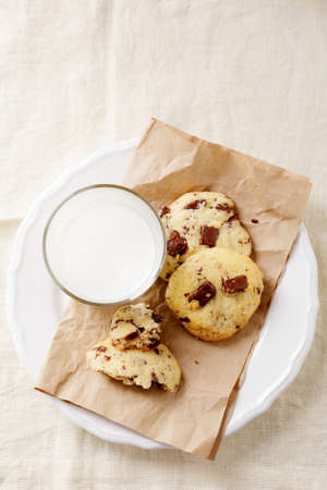 Rustic cookies on a paper with glass of milk, dessert. Top view photo