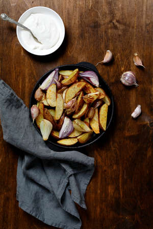 Baked potato slices with garlic and onion. Top view photo