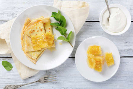 Sweet pancakes with honey on a plate, dessert. Top view photo
