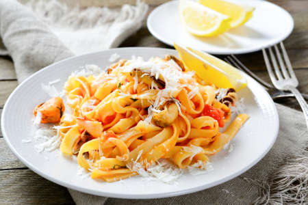 Pasta with seafood on a plate on wooden background photo