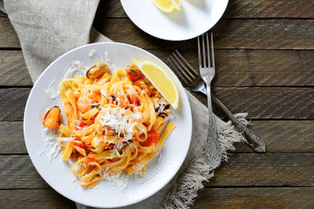 Italian pasta with seafood on a white plate on wooden background