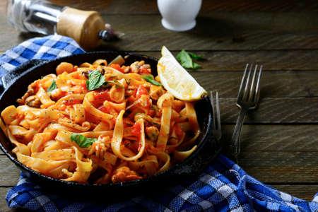 Spaghetti ai frutti di mare in una padella, cucina mediterranea