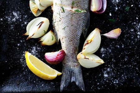 mariscos: Pescado al horno con limón y cebolla en una bandeja de horno, mariscos