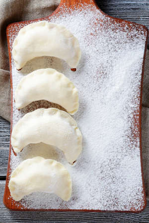 Uncooked dumplings on the cutting board. Homemade food photo