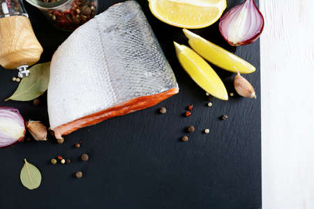 Raw Salmon steak on slate with lemon and spices - diet, healthy food and cooking concept photo