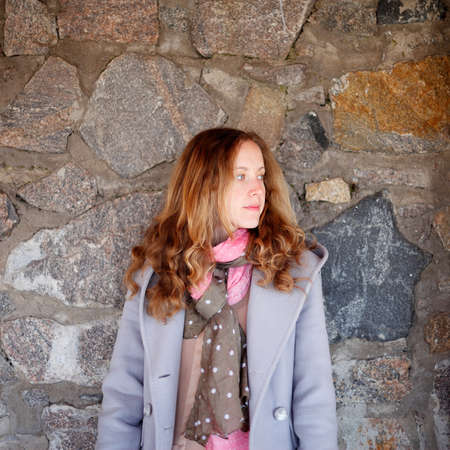 Portrait of young woman against a stone wall. Outdoor photo