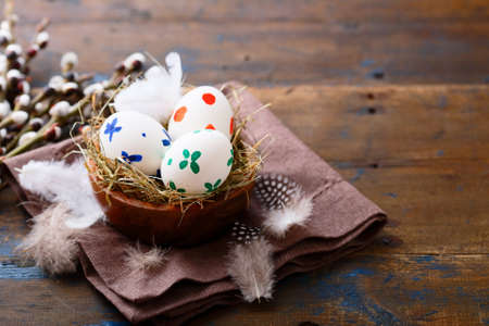 straw twig: Painted Easter eggs in a nest on napkin. Spring celebration concept