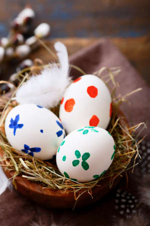 straw twig: Easter eggs in a nest on napkin. Spring holiday