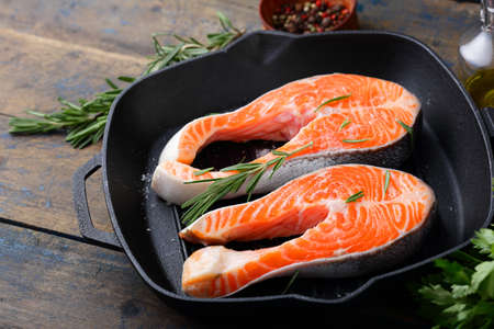 dog salmon: Steak Raw Salmon on a griddle pan on wooden table