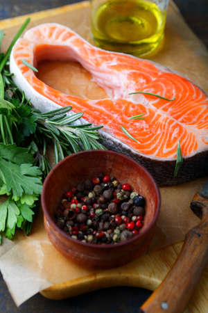 dog salmon: Raw Steak Salmon, greens and spice on a cutting board. Cooking red fish
