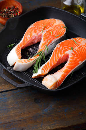 dog salmon: Steak Salmon on a griddle pan on wooden table