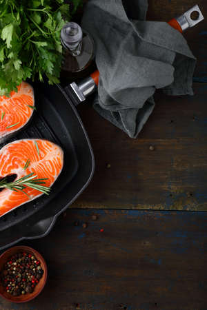 griddle: Raw Salmon Steak in steel griddle on wooden table Stock Photo