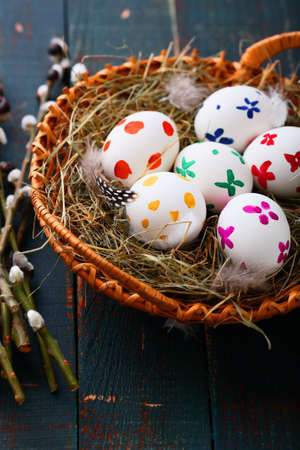 straw twig: Easter eggs in wicker basket and willow branches on wooden table. Spring holiday