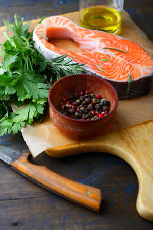 red  fish: Raw Red Fish, parsley, rosemary and spice on a cutting board. Cooking Salmon