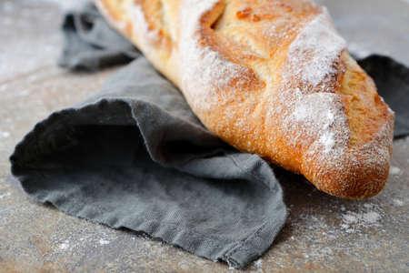 artisan bakery: One Baguette on the slate on napkin. Closeup