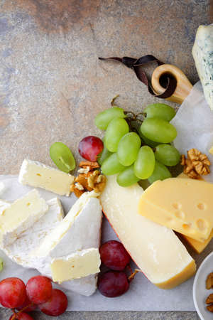 different types of cheese: Different types of cheese with grapes and walnuts on the slate background. Top view