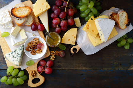 different types of cheese: Composition of different types cheese on old wooden boards. Top view